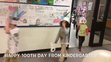 Kindergarteners marching around the school on 100th day