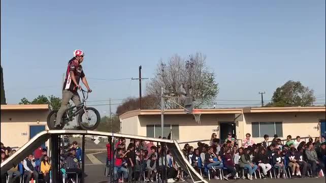 BMX biker attempts a jump over teachers in pep rally