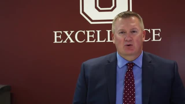 video of Mr. Bearup speaking in front of maroon wall with G logo
