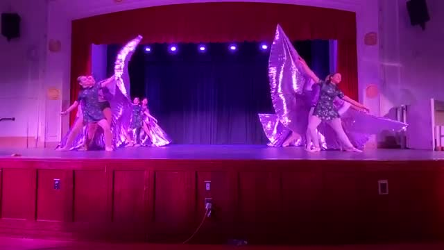 students on stage with light up flowy wings dancing as butterflies