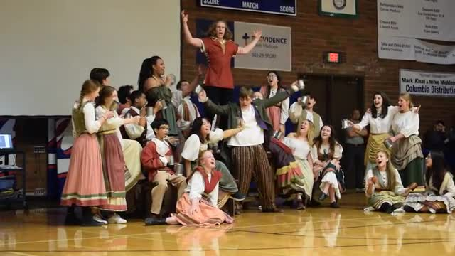 students dressed in 18th-century costumes sing a song while dancing around a school gym