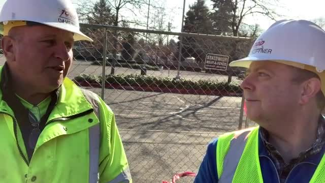 man in hard hat walks around construction site
