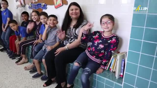 Elementary students and teacher waving hello