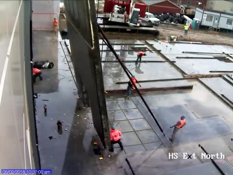 crane lifts wall of gym during construction