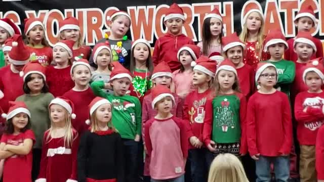 1st Graders, dressed in red and green and Santa hats, singing