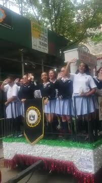 Girls in white and blue uniforms smile and wave on a float
