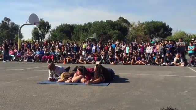 A video of BMX performers performing tricks, awing the crowd as they jump over four Stonegate teachers.