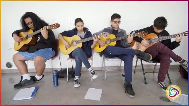 Video featuring a compilation of images from Tierra Adentro of New Mexico Charter School. Opening caption is white test on a black background: Discover yourself at Tierra Adentro a public arts charter school serving grades 6-12. Dancers in jackets perform in front of a crowd, a student reads at their desk, four guitarists practice while seated, graduation scenes of students in caps and gowns. Aerial footage of Albuquerque, New Mexico appears followed by more footage of students performing flamenco and Spanish folk dance, and students working on art projects at their desks in the classroom. The final title card is white text on a black background, and read