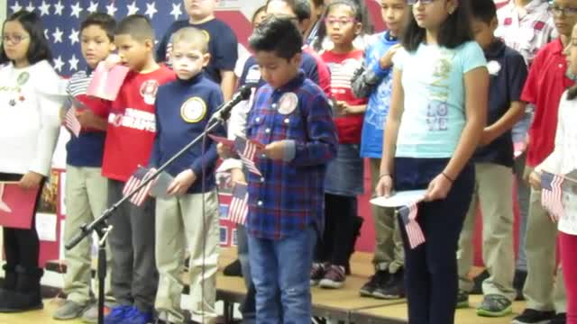 Mrs. L's 4th grade class reading their writing during the veterans assembly