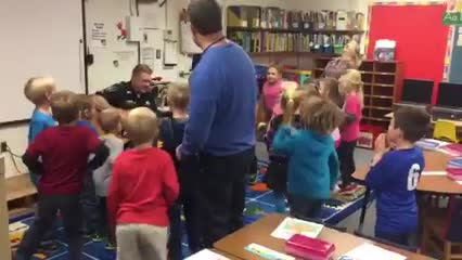 Students dancing with Mr. Lance and listening to Officer Hebb sing during Red Ribbon week celebrations.